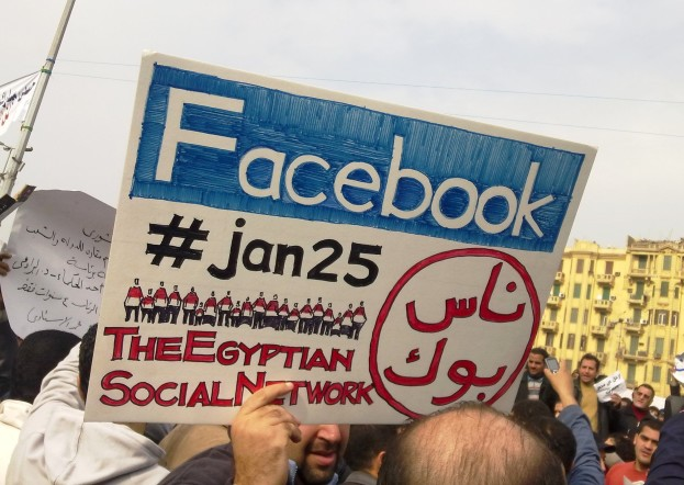 """A man during the 2011 Egyptian protests carrying a card saying """"Facebook, #jan25 CC BY-SA 3.0"""